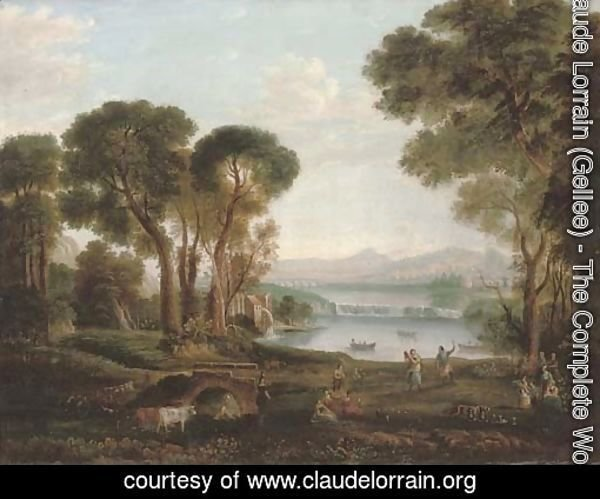 An Italianate river landscape with figures dancing and making music on a bank, a town beyond